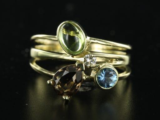 ringen naast elkaar te dragen aan elkaar bevestigen goud met edelsteen en diamant