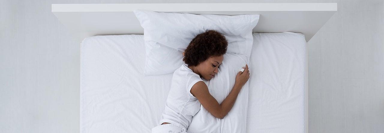 persoon slaapt op witte boxspring met kussens bedworld